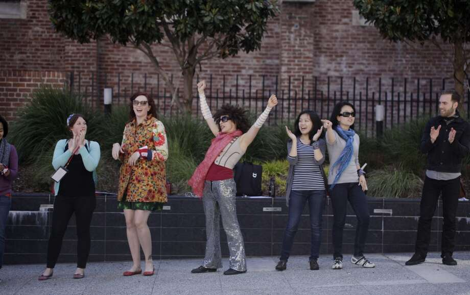 Working a station at a corporate team building gig, Naomi Hummel teaches a group of Google employees to do a dance called the Funky Pizza in front of the Jewish Contemporary Museum.