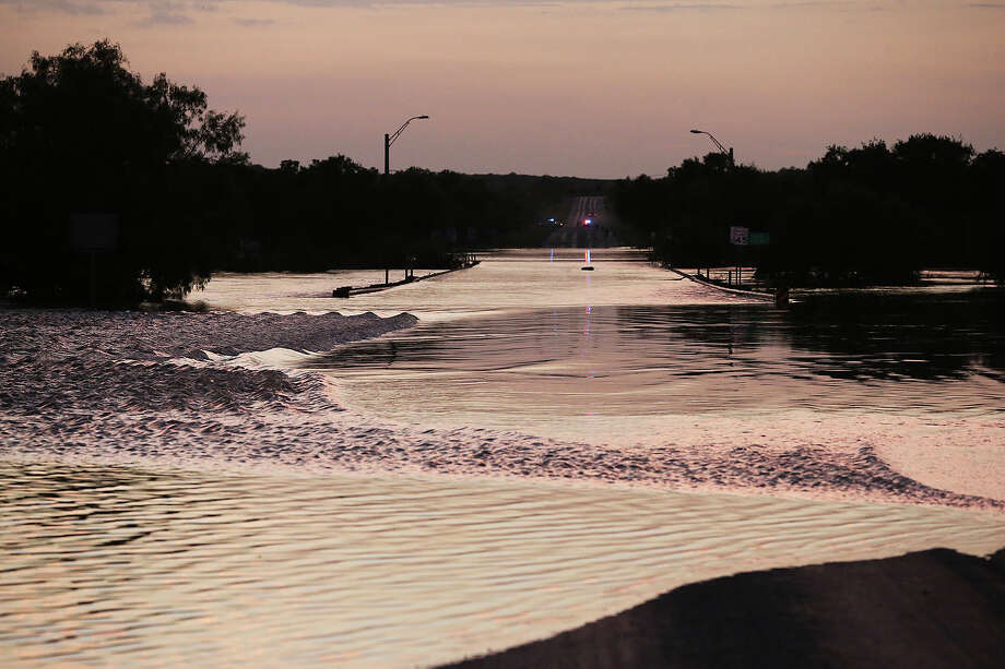 Elm Creek floods over the 2777 north bridge preventing traffic from leaving Eagle Pass to Del Rio at Sunset when the water was still rising during cleanup in the aftermath of flooding in Eagle Pass.  on  June 16, 2013. Photo: TOM REEL