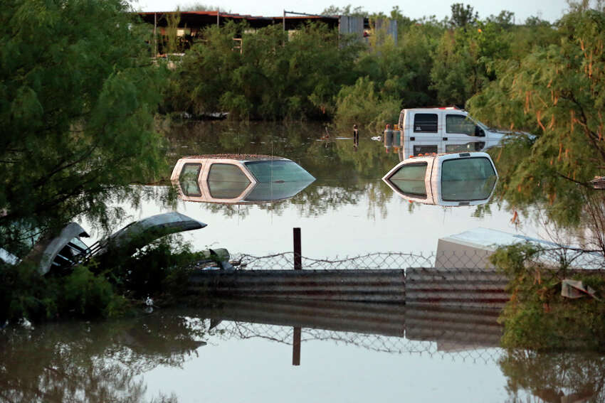 A salvage yard next to Elm Creek remains under water during cleanup in the aftermath of flooding in Eagle Pass. on June 16, 2013.