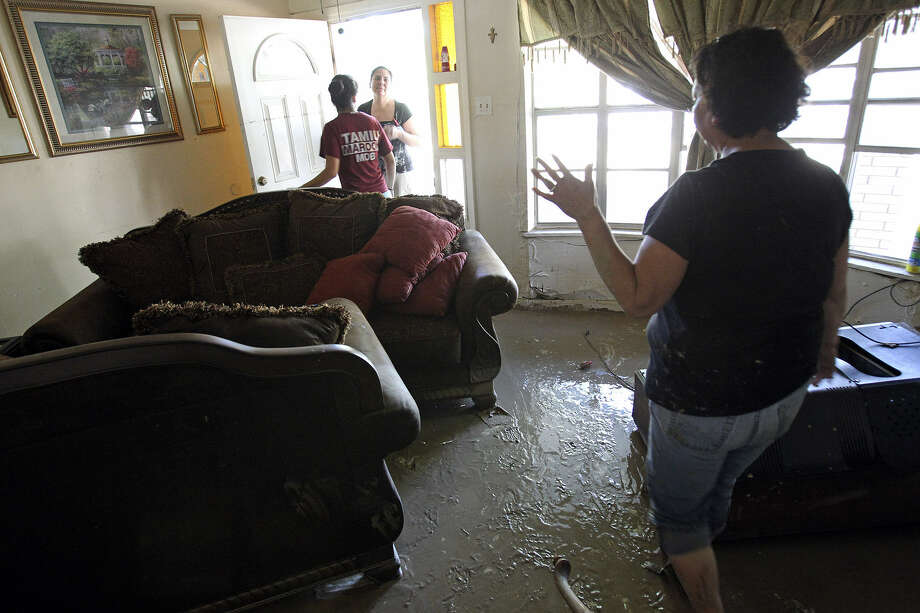 Alicia Vargas walks through her flooded home while Gabriella Gallegos greets another family member, Lupita Cardenas, at the front door. Flooding in Eagle Pass came after 16.65 inches of rain fell in 36 hours. Photo: Photos By Tom Reel / San Antonio Express-News