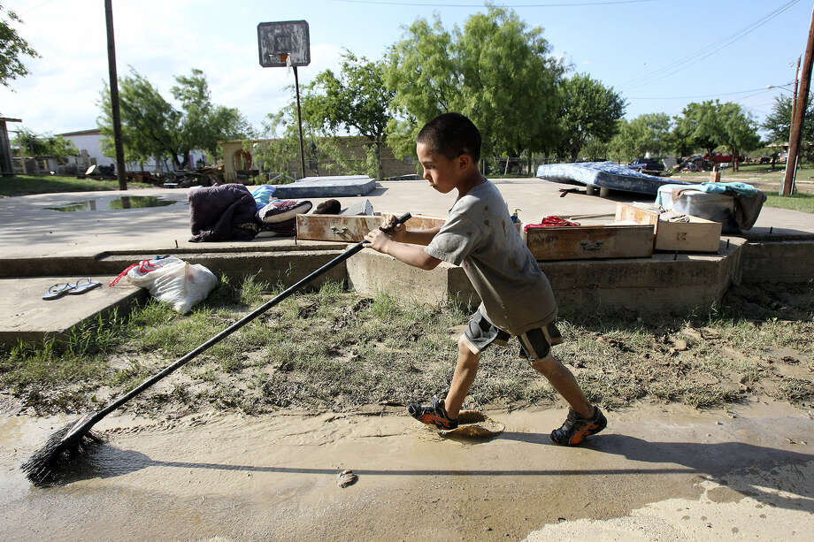 Matthew Cardenas helps sweep mud and water from his relatives' home on Barrera Street, one of the hardest-hit areas.