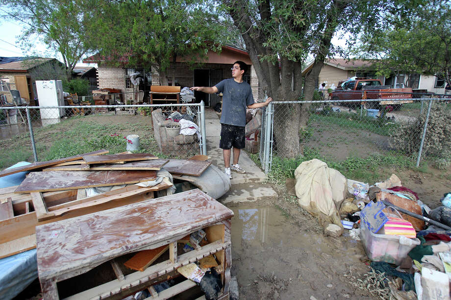 Ricky Gonzalez looks down the street over the entire contents of his grandmother's home put out on the road during cleanup in the aftermath of flooding in Eagle Pass.  on  June 16, 2013. Photo: For The San Antonio Express-News