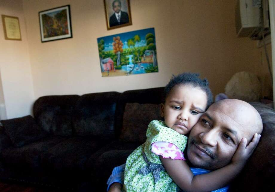 Emmanuel Doreste and his daughter Ayanna Doreste, 2, in their Stamford home.  Doreste is originally from Haiti and is waiting to hear from several family members who either live or were visiting the area of the earthquake. Photo: Kathleen O'Rourke / Stamford Advocate
