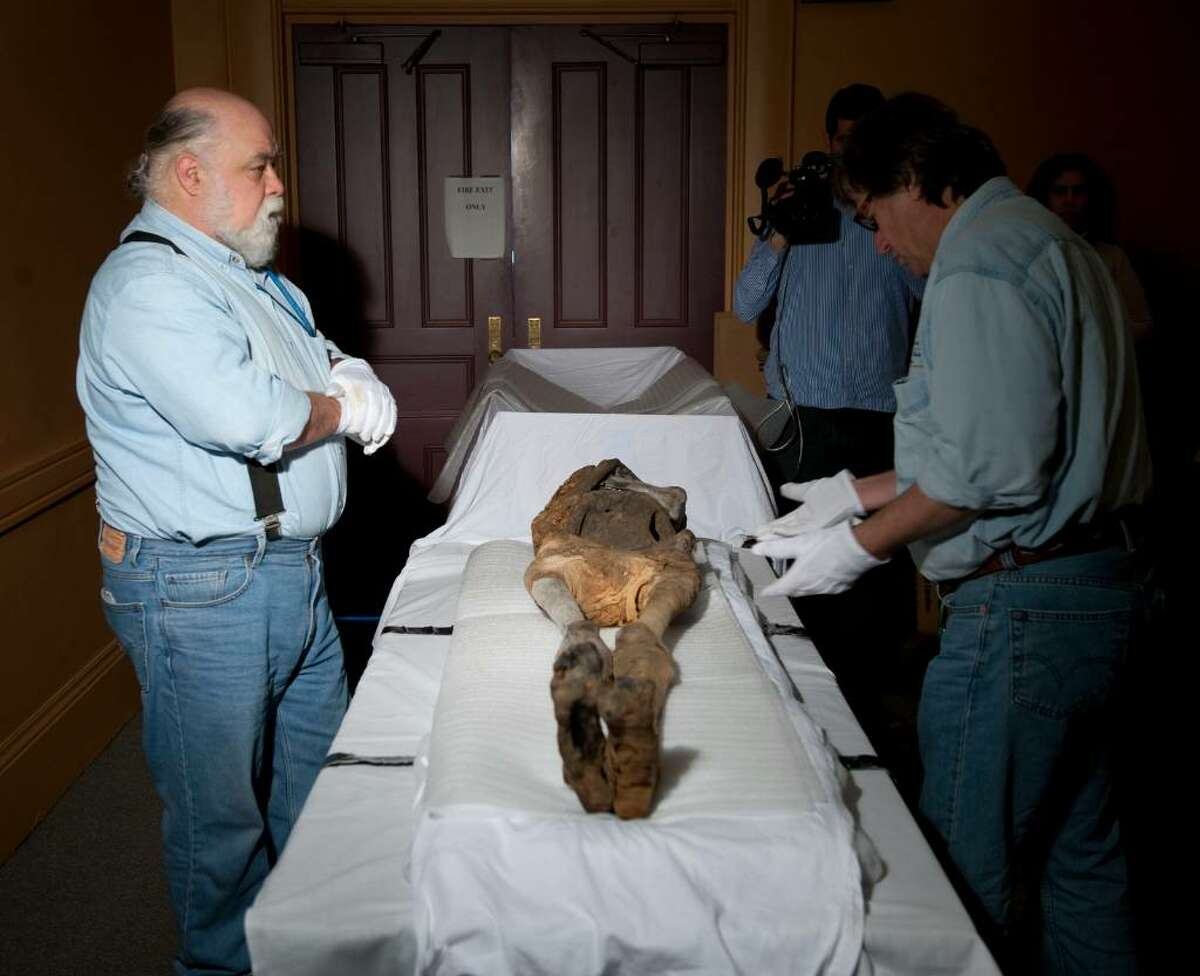 In this Tuesday, Jan. 12, 2010 photo, Quinnipiac University Professors Gerald Conlogue left, and Ronald Beckett, co-directors of the Bioanthropology Research Institute at Quninnipiac wrap a torso of a mummy for shipping to their school at the Barnum Museum in Bridgeport, Conn. (AP Photo/Douglas Healey).