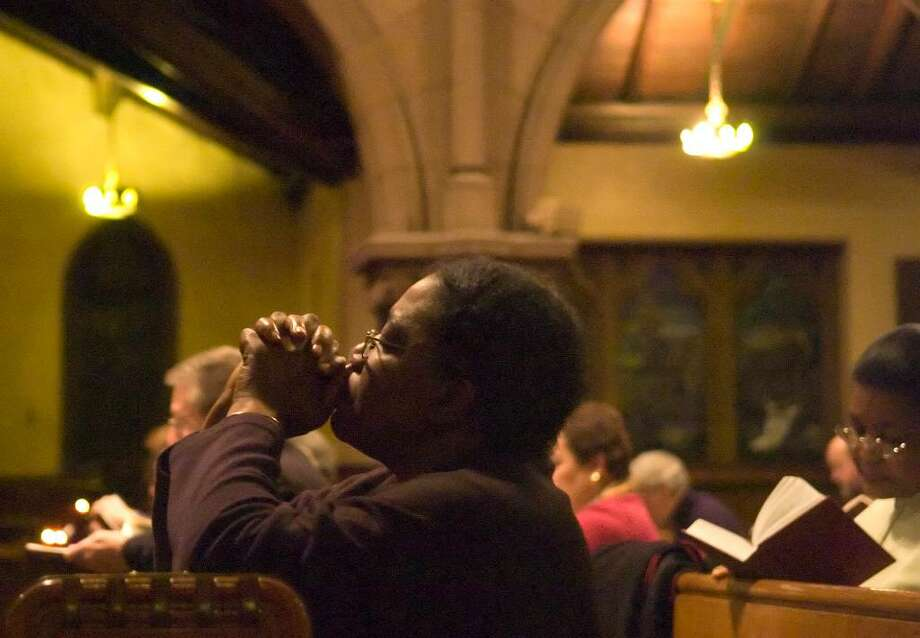 Cynthia Rowe kneels in prayer during prayer service at St. John's Episcopal Church for the victims of this week's earthquake in Haiti. St. John's is also home to L'Eglise de L'Epiphanie an Haitian Episcopalian congregation. Photo: Chris Preovolos / Stamford Advocate