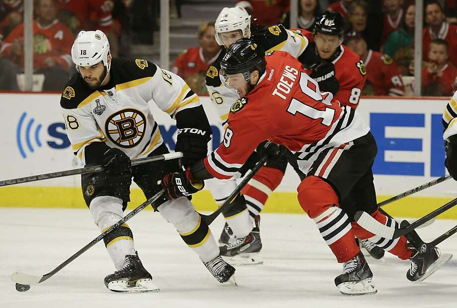 Chicago Blackhawks center Jonathan Toews (19) reaches to control the puck against Boston Bruins right wing Nathan Horton (18) in the second period during Game 2 of the NHL hockey Stanley Cup Finals, Saturday, June 15, 2013, in Chicago. (AP Photo/Nam Y. Huh) Photo: Nam Y. Huh, Associated Press