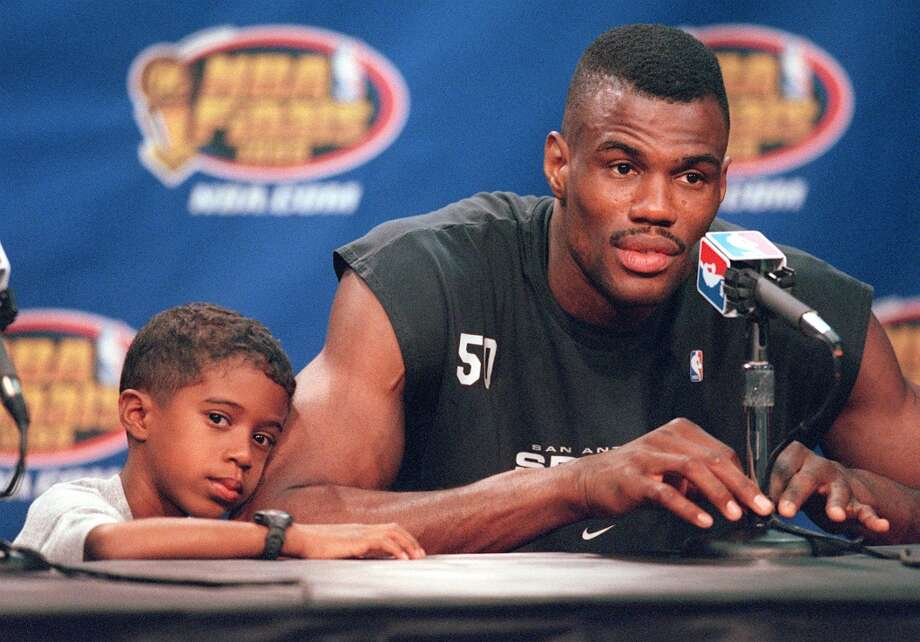 ... and David Robinson Jr. He's seen here laying his head on his father's arm during a media interview session after the Spurs' practice at the Alamodome in 1999.