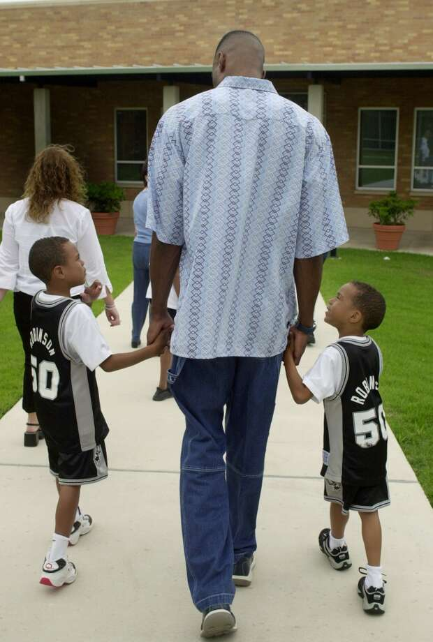 ... and Justin Robinson(right). He's seen here walking with Dad and brother Corey (left) following a news conference in San Antonio, on May 24, 2002, where Robinson announced his retirement.