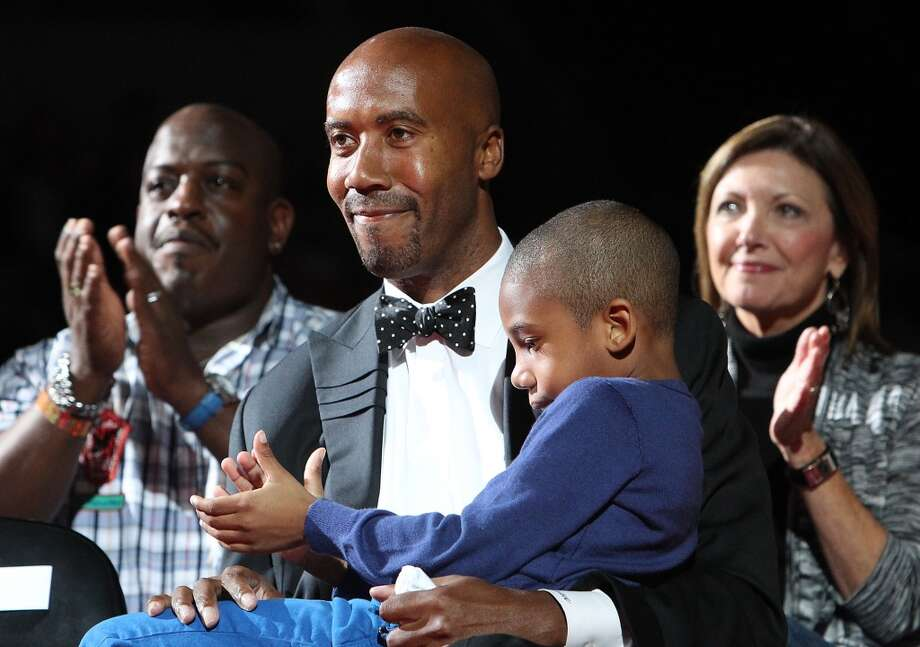 Former Spurs forward Bruce Bowen is joined by his son Ojani while being honored in a ceremony after the Spurs-Minnesota Timberwolves game at the AT&T Center on March 21, 2012.