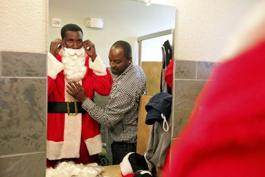 Greg Blair helps his son former Spur (and current Maverick) DeJuan Blair put on a Santa Claus costume before taking part in the Elf Louise Christmas project on Dec. 23, 2011,  at the Rosemont at Highland Park Apartments.