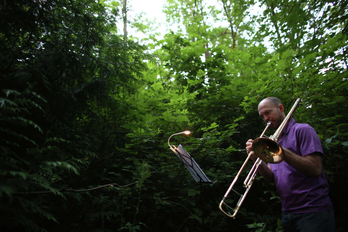 Christian Pincock plays the valve trombone during a mini symphony concert in the woods of Ravenna Park ravine in Seattle. During the concert, performers played excerpts from composer Nat Evans'
