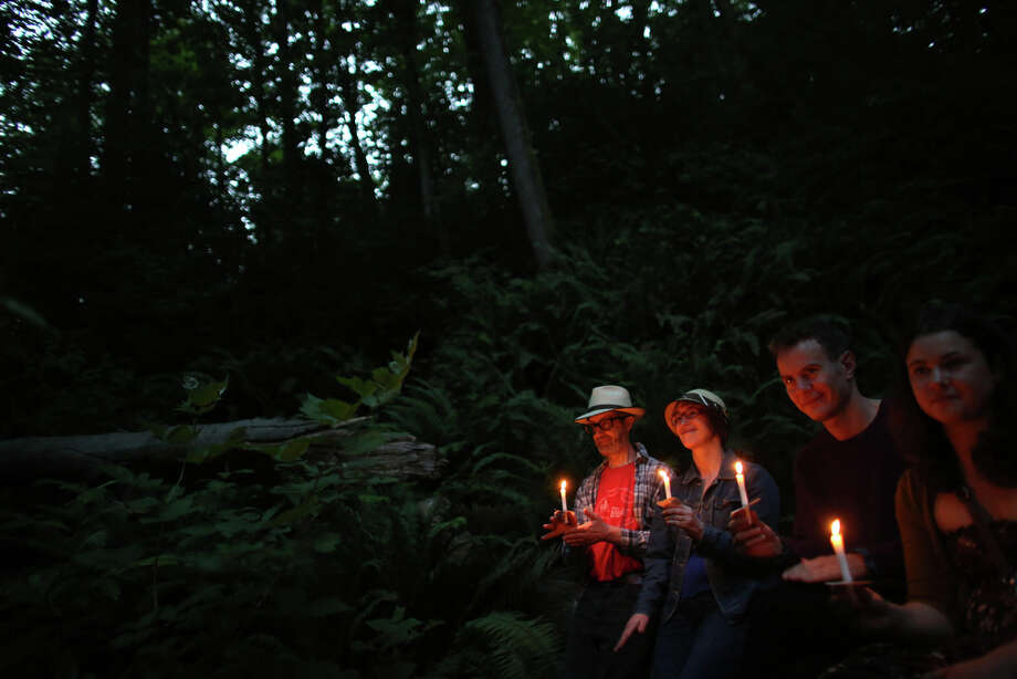 "From left, Keith and Karen Eisenbrey, William Walker and Kaia Chessen hold candles during a mini symphony concert in the woods of Ravenna Park ravine in Seattle. During the concert, performers played excerpts from composer Nat Evans' ""Hungry Ghosts."" The song was performed by candlelight. Photographed on Saturday, June 15, 2013. Photo: JOSHUA TRUJILLO, SEATTLEPI.COM / SEATTLEPI.COM"