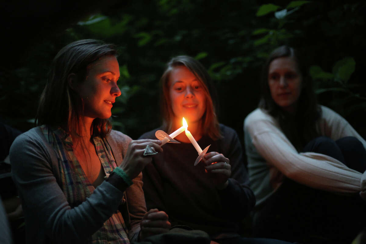 From left, Natalie Thompson, Amelia Apfel and Kate Meyer light candles during a mini symphony concert in the woods of Ravenna Park ravine in Seattle. During the concert, performers played excerpts from composer Nat Evans'