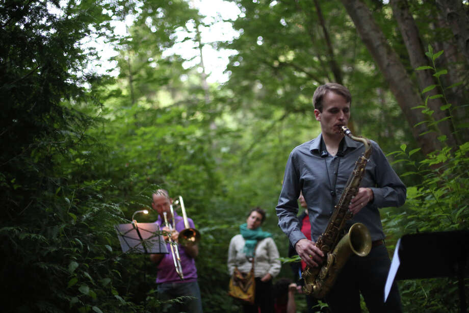 "Neil Welch plays the sax during a mini symphony concert in the woods of Ravenna Park ravine in Seattle. During the concert, performers played excerpts from composer Nat Evans' ""Hungry Ghosts."" The song was performed by candlelight. Photographed on Saturday, June 15, 2013. Photo: JOSHUA TRUJILLO, SEATTLEPI.COM / SEATTLEPI.COM"
