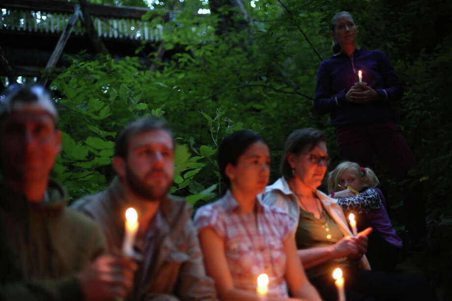 "People hold candles during a mini symphony concert in the woods of Ravenna Park ravine in Seattle. During the concert, performers played excerpts from composer Nat Evans' ""Hungry Ghosts."" The song was performed by candlelight. Photographed on Saturday, June 15, 2013. Photo: JOSHUA TRUJILLO, SEATTLEPI.COM / SEATTLEPI.COM"