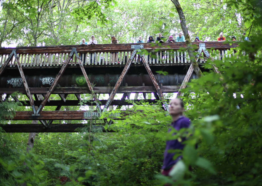 "People watch from a pedestrian bridge overhead during a mini symphony concert in the woods of Ravenna Park ravine in Seattle. During the concert, performers played excerpts from composer Nat Evans' ""Hungry Ghosts."" The song was performed by candlelight. Photographed on Saturday, June 15, 2013. Photo: JOSHUA TRUJILLO, SEATTLEPI.COM / SEATTLEPI.COM"