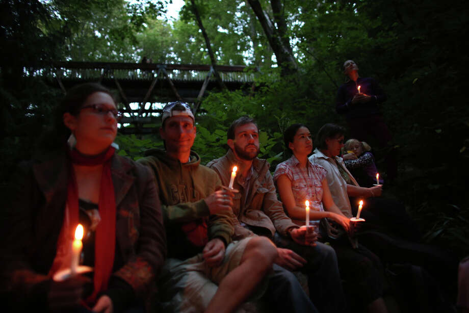 "People hold candles during a mini symphony concert in the woods of Ravenna Park ravine in Seattle. During the concert, performers played excerpts from composer Nat Evans' ""Hungry Ghosts."" The song was performed by candlelight. Photographed on Saturday, June 15, 2013. You can read our story about the performance by clicking here. Photo: JOSHUA TRUJILLO, SEATTLEPI.COM / SEATTLEPI.COM"