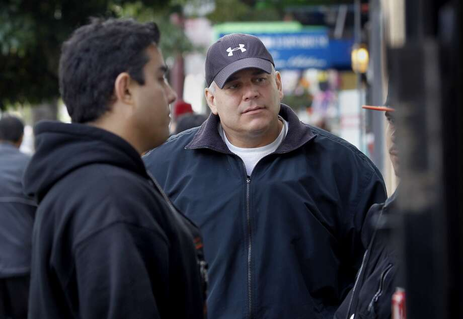 Police officers John Cathey (right) and David Sands talk with a young suspected gang member on Mission Street Wednesday June 05, 2013. Mission district police station officers John Cathey and David Sands are taking a new approach to tackling gang violence in San Francisco, Calif. by getting suspected gang members real employment.