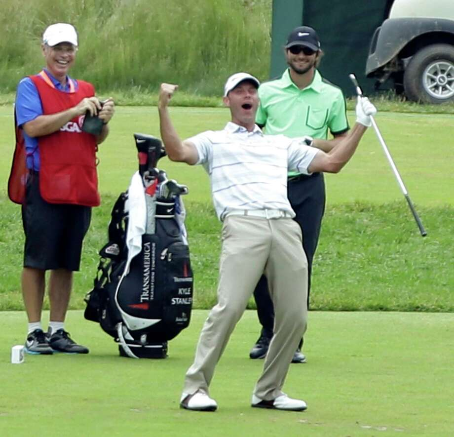 Shawn Stefani, center, reacts after hitting a hole in one on the 17th hole during the fourth round of the U.S. Open golf tournament at Merion Golf Club, Sunday, June 16, 2013, in Ardmore, Pa. (AP Photo/Julio Cortez) Photo: Julio Cortez, Associated Press / AP