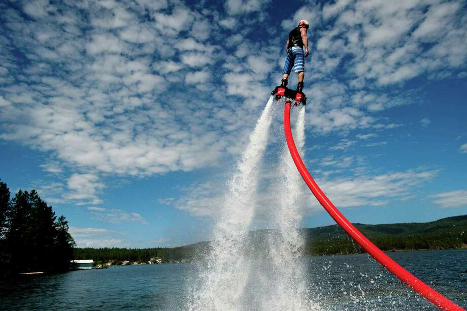 Shane Jenkins of AV Watersports stands on a Fly Board as he gains altitude during a demonstration of the contraption, which uses water pressurized by a personal watercraft's water pump to lift the operator out of the water on Thursday, June 13, 2013, on Long Lake in Nine Mile Falls, Wash. (AP Photo/The Spokesman-Review, Tyler Tjomsland)  Photo: AP