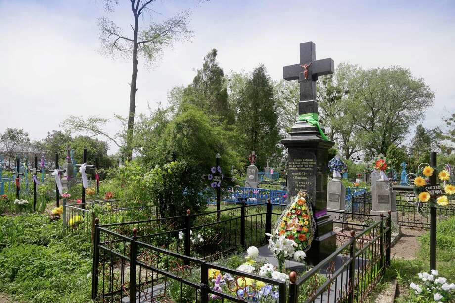 "In this picture taken May 10, 2013, a monument pays tribute to civilians who were burned alive during WWII in Pidhaitsi close to Ukraine's western city of Lutsk. The monument reads: ""To our parents, wives, children, who were murdered by the German occupants on December 3, 1943 in Pidhaitsi. 21 people, including 9 children."" Evidence uncovered by AP indicates that Ukrainian Self Defense Legion commander Michael Karkoc's unit was in the area at the time of the massacre. Photo: AP"
