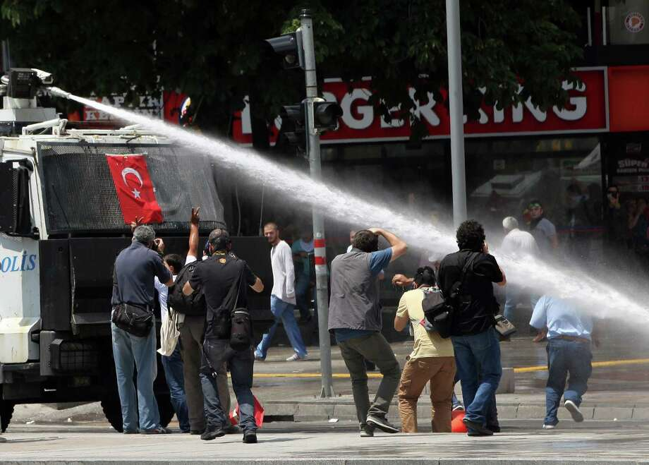Turkish riot police spray water cannon at demonstrators who remained defiant after authorities evicted activists from an Istanbul park, making clear they are taking a hardline against attempts to rekindle protests that have shaken the country, in city's main Kizilay Square in Ankara, Turkey, Sunday, June 16, 2013. Photo: AP