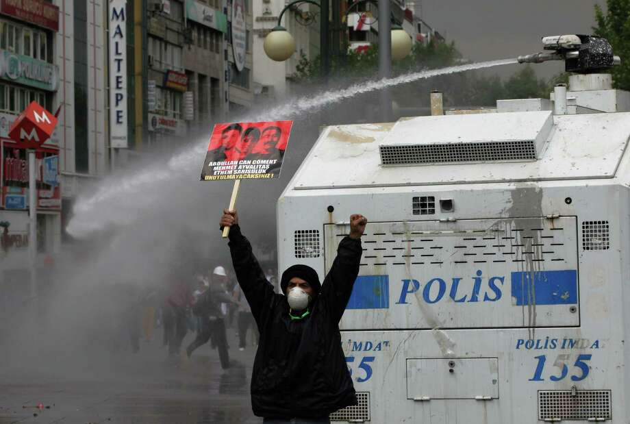 A protester holds up a banner with photos of three victims killed during protests and shouts anti-government slogans as Turkish riot police spray water cannon at demonstrators who remained defiant after authorities evicted activists from an Istanbul park, making clear they are taking a hardline against attempts to rekindle protests that have shaken the country, in city's main Kizilay Square in Ankara, Turkey, Sunday, June 16, 2013. Photo: AP