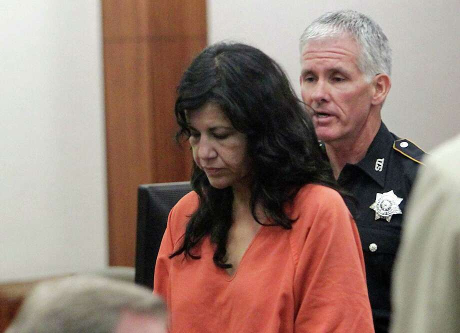 In this Tuesday, June 11, 2013 photo, Ana Lilia Trujillo left, is escorted by a bailiff from Judge Brock Thomas' 338th State District Court, in Houston. A prosecutor says Trujillo accused of stabbing her boyfriend to death with her stiletto heel had been drinking tequila with him at a nightclub earlier. (AP Photo/Houston Chronicle, James Nielsen)  Photo: AP