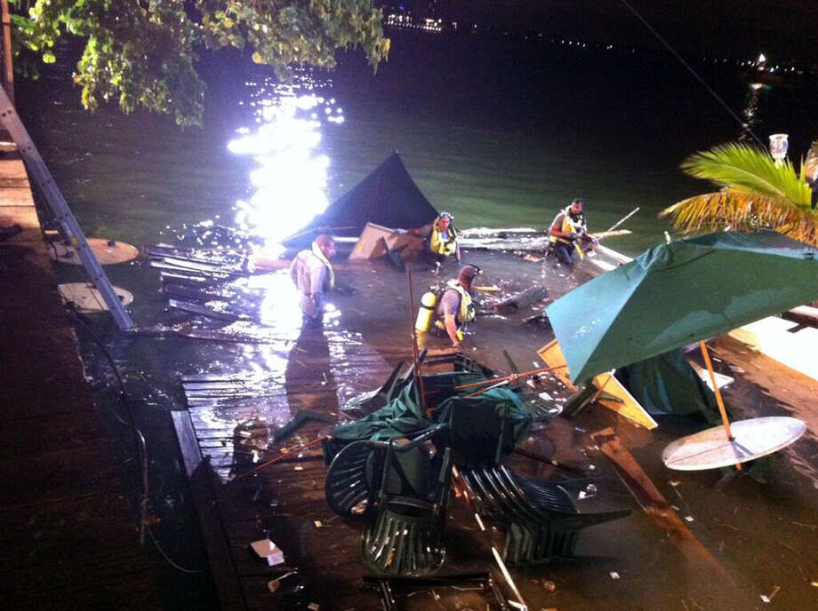 In this photo provided by WSVN-TV, divers search the water after a deck collapse  at Shuckers Bar & Grill in Miami Thursday night, June 13, 2013.  The deck collapsed during the NBA Finals on Thursday night, sending dozens of patrons into the shallow waters of Biscayne Bay. Three people were critically injured. (AP Photo/WSVN-TV, Tom Tuckwell) Photo: AP