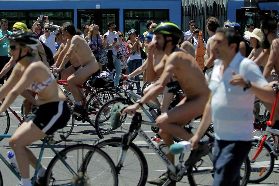 People watch as cyclists ride naked through Madrid, Saturday, June 15, 2013. Cyclists demonstrate against cars and to promote the use of bicycles and to highlight the danger due to lack of cycling lanes in the capital. Photo: AP