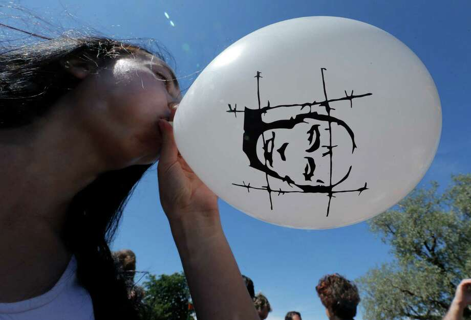 An opposition protester inflates a balloon depicting Russian President Vladimir Putin behind barbed wire during a protest rally in St.Petersburg, Russia, Wednesday, June 12, 2013. Wednesday's rally is in support of 27 people who face charges related to a protest that turned violent on the eve of Putin's inauguration more than a year ago. Photo: AP