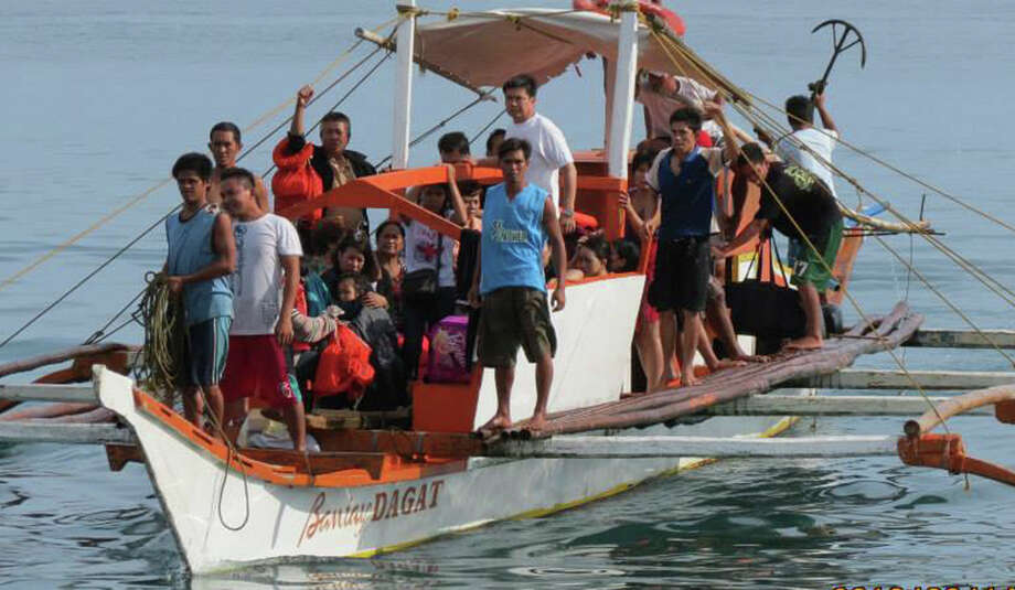 In this Friday June 14, 2013 photo, passengers who survived the sinking of the ferry M/V Carmel prepare to disembark from a rescue boat at the port of Aroroy township, Masbate province in central Philippines. The ferry, was going from Albay province in the center of the Philippines to the nearby Masbate province when it sank, killing two people but 54 passengers and crew members were saved when rescuers pulled them to safety about 1 nautical mile from Aroroy port. Rescuers continue to search for seven more missing passengers Saturday. (AP Photo/Local Government Unit Masbate, Neri Jazul)  Photo: AP