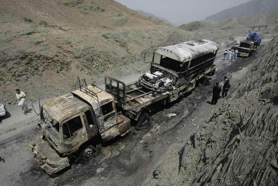 Pakistani security personnel and villagers look at gutted NATO trucks in Pakistan's tribal region of Khyber on Monday, June 10, 2013. A Pakistani official says a rocket attack targeting NATO supply trucks in the country's northwest has killed several people. Photo: AP
