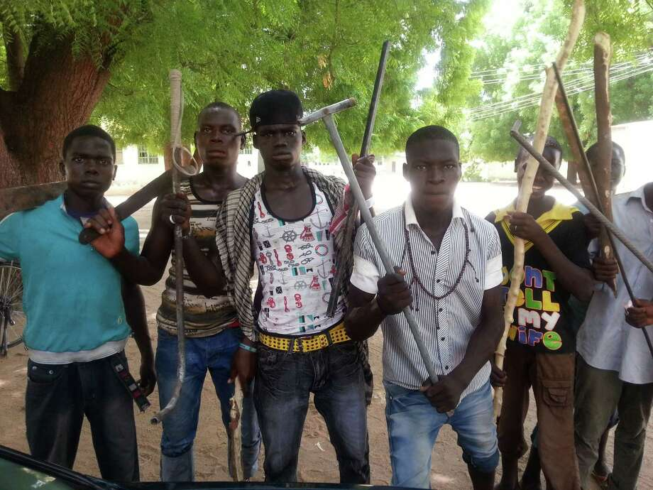 "In this photo taken with a mobile phone Tuesday, June 11, 2013, Vigilantes youths pose for a photographs in Maiduguri, Nigeria. As soldiers continue an offensive against radical Islamic extremists in northeast Nigeria, young men armed with machetes and sticks have now entered the streets of the region's biggest city, targeting suspected fighters. The members of the ""Civilian JTF,"" a play off the acronym used to describe the joint military and police taskforce in the region, already have come under attack from extremists for pointing out suspects to soldiers. However, it remains unclear what happens to those the group points out, as some suspects in Maiduguri have already been shot dead by security forces and left rotting in ditches in the city. Photo: AP"