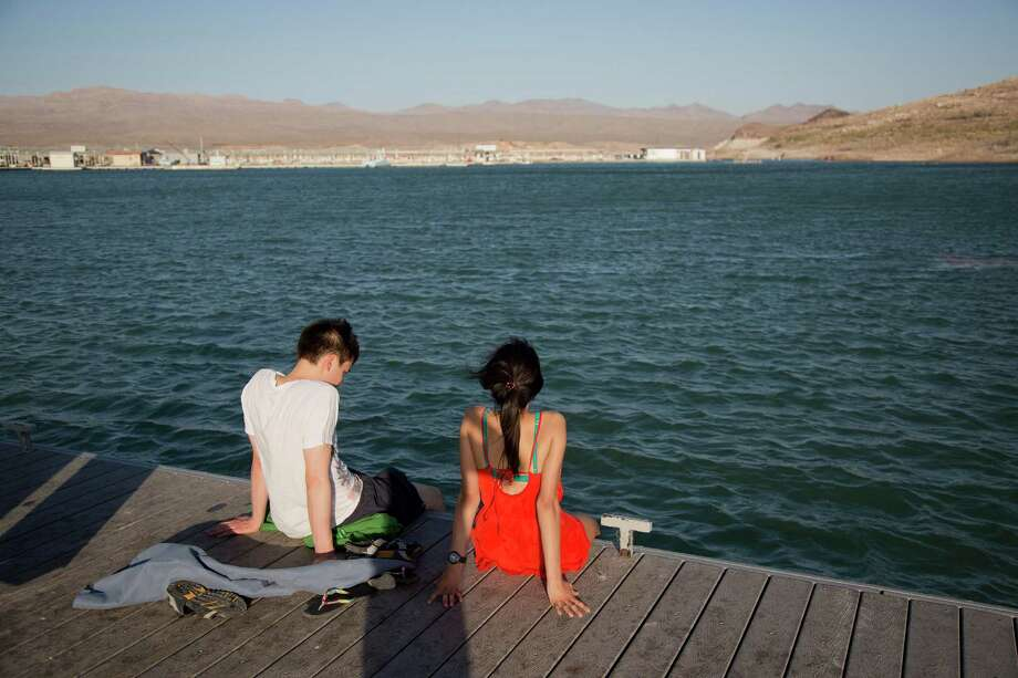 Samuel Nguyen, left, and Mila Phaman, of Montreal, Canada, dip their feet in the water at Echo Bay Marina Monday, June 10, 2013, at Lake Mead National Recreation Area near Overton, Nev. Authorities are warning people to avoid the Overton Arm section of Lake Mead after park officials found dead carp and a mysterious foam there. The foam appeared to be coming from the mouth of the Virgin River and stretched about eight miles down to Echo Bay. Photo: AP