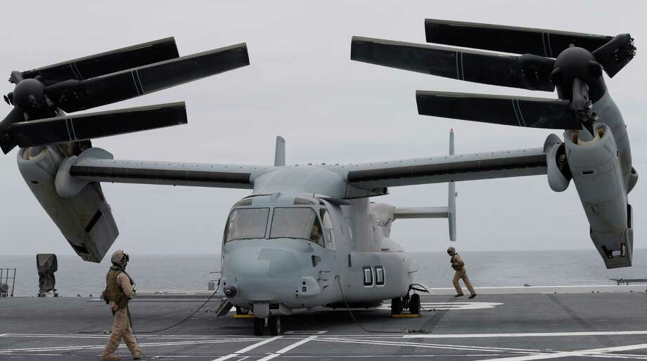 Marines secure an MV-22 Osprey aircraft as it folds to be lowered into the hanger aboard the Japanese destroyer JS Hyuga in coastal waters off San Diego Friday, June 14, 2013, in San Diego. A U.S. Marine Corps MV-22 Osprey aircraft made an unprecedented landing on a Japanese naval vessel off the California coast Friday, despite protests in Japan over concerns of the tilt-rotor aircraft's safety record. Photo: AP