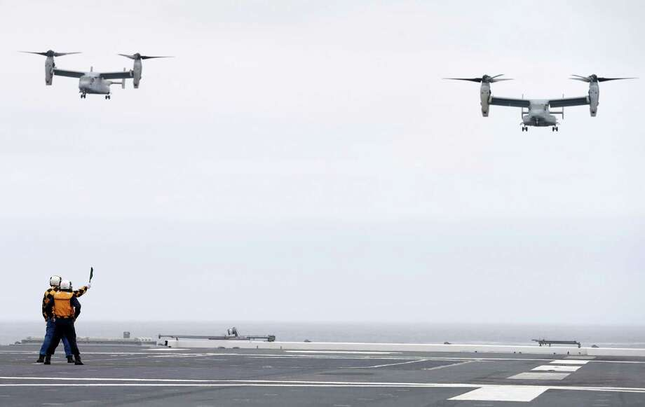 A Marine MV-22 Osprey aircraft, right, is guided in for a landing by Japanese sailors, left, as it lands on the Japanese destroyer JS Hyuga Friday, June 14, 2013, in coastal waters off San Diego. Another Osprey follows at left. The aircraft made an unprecedented landing on the vessel Friday, despite protests in Japan over concerns over the tilt-rotor aircraft's safety record. Photo: AP