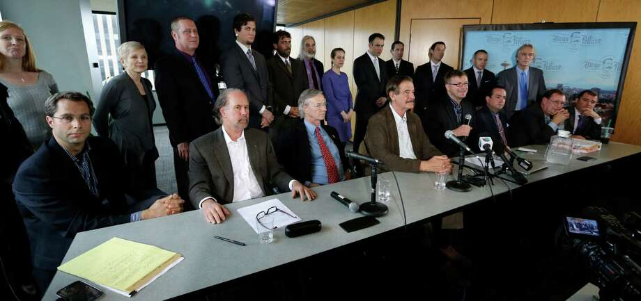 In this photo taken May 30, 2013, Jamen Shively, CEO of Diego Pellicer, seated fourth from right and holding a microphone, speaks during a news conference in Seattle. With visionary zeal, Shively described plans to quickly raise $10 million and to eventually build his company, Diego Pellicer, into an international pot powerhouse and eventually move into the recreational market.  But his arrangement with the Seattle medical marijuana company, Northwest Patient Resource Center, was troubling enough to one of its owners, Thomas Jun, that he is walking away from the deal _ and the company he helped found _ because he fears it puts everyone involved at risk of federal prosecution. Photo: AP