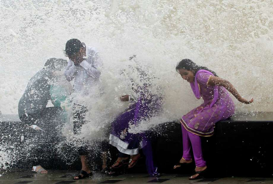 People enjoy high tide waves during monsoon rains on the Arabian Sea coast in Mumbai, India, Wednesday, June 12, 2013. Monsoon rains, that lash India from June to September, are considered crucial for farmers whose crops feed millions of people. Photo: AP