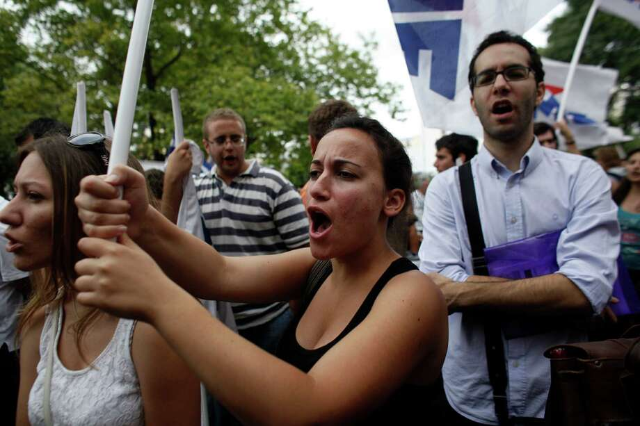 Protesters shout slogans during  a rally outside the Greek state television ERT headquarters during a 24-hour general strike in Athens, on Thursday, June 13, 2013. Greece's fragile governing coalition failed to reach a compromise Wednesday about the closure of the state-run ERT broadcaster. That left the government in a crisis that could lead to early elections, just a year after it was formed to save the country from bankruptcy. Photo: AP