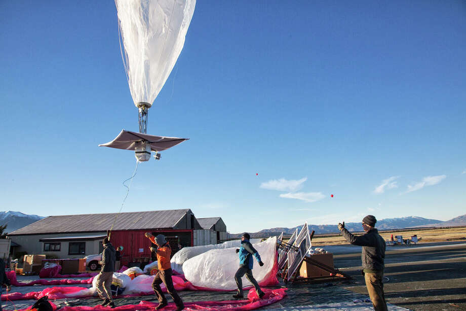 In this June 10, 2013 photo released by Google, a Google team releases a balloon in Tekapo, New Zealand. Google is testing the balloons which sail in the stratosphere and beam the Internet to Earth. (AP Photo/Google, Andrea Dunlap) Photo: AP