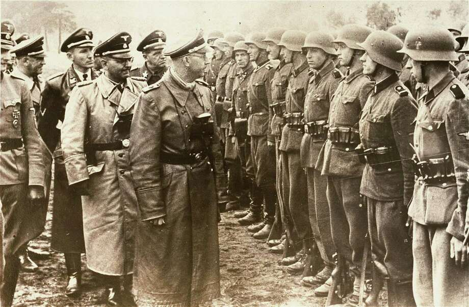 The June 3, 1944 photo provided by the US Holocaust Memorial Museum shows Heinrich Himmler, centre,  SS Reichsfuehrer-SS, head of the Gestapo and the Waffen-SS, and Minister of the Interior of Nazi Germany from 1943 to 1945, as he reviews troops of the Galician SS-Volunteer Infantry Division   Michael Karkoc  a top commander whose Nazi SS-led unit is blamed for burning villages filled with women and children lied to American immigration officials to get into the United States and has been living in Minnesota since shortly after World War II, according to evidence uncovered by The Associated Press. Michael Karkoc became a member of the Galician division after the Ukrainian Self Defense Legion was incorporated into it near the end of the war. Photo: AP