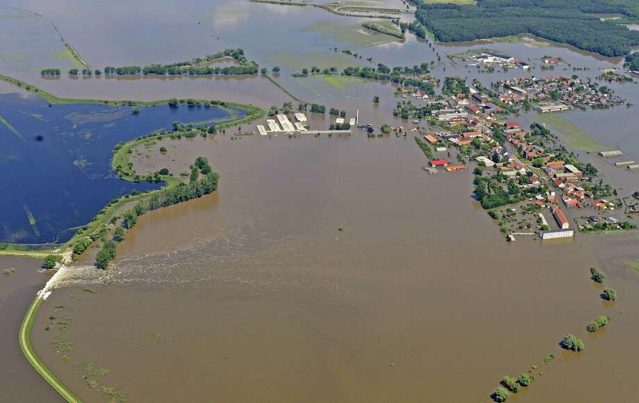 The bursting of a dike, left, has led to the flooding of the village Fischbeck, central Germany, Tuesday, June 11, 2013. Weeks of heavy rain this spring have sent the Elbe, the Danube and other rivers such as the Vltava and the Saale overflowing their banks, causing extensive damage in central and southern Germany, the Czech Republic, Austria, Slovakia and Hungary. Photo: AP