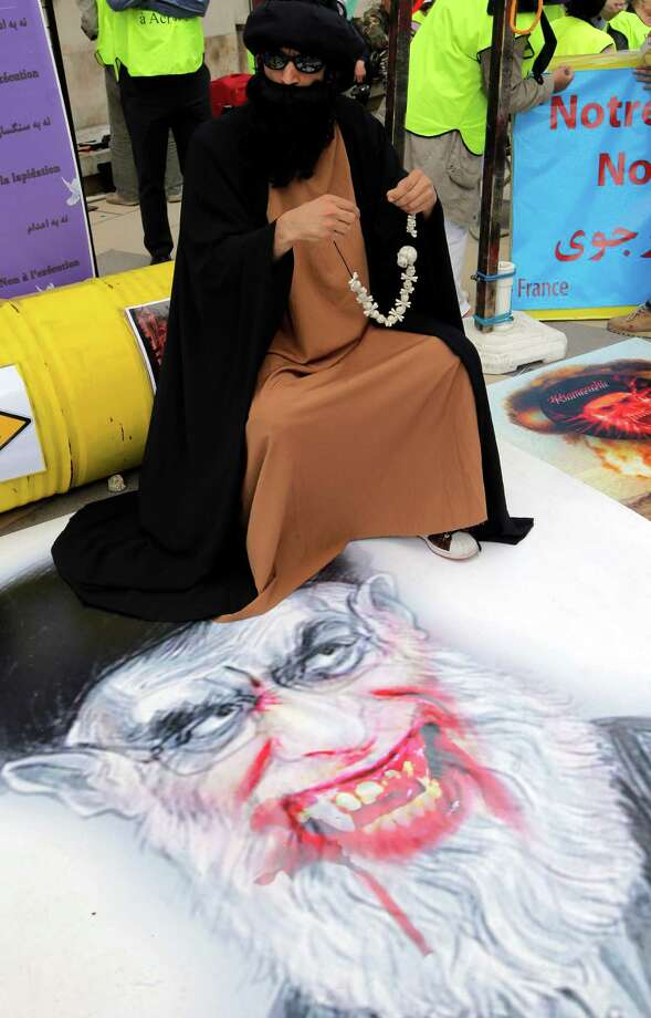 A demonstrator sits on a cartoon of supreme leader Ayatollah Ali Khamenei as supporters of Maryam Rajavi, the President of National Council of Resistance of Iran demonstrate on Trocadero Plaza in Paris, Friday, June 14, 2013. Iran holds presidential elections on Friday, June 14, to choose a successor to Mahmoud Ahmadinejad, who cannot run for a third consecutive term in office. Six candidates remain in the race, a moderate, four conservatives and a hard-liner. Photo: AP