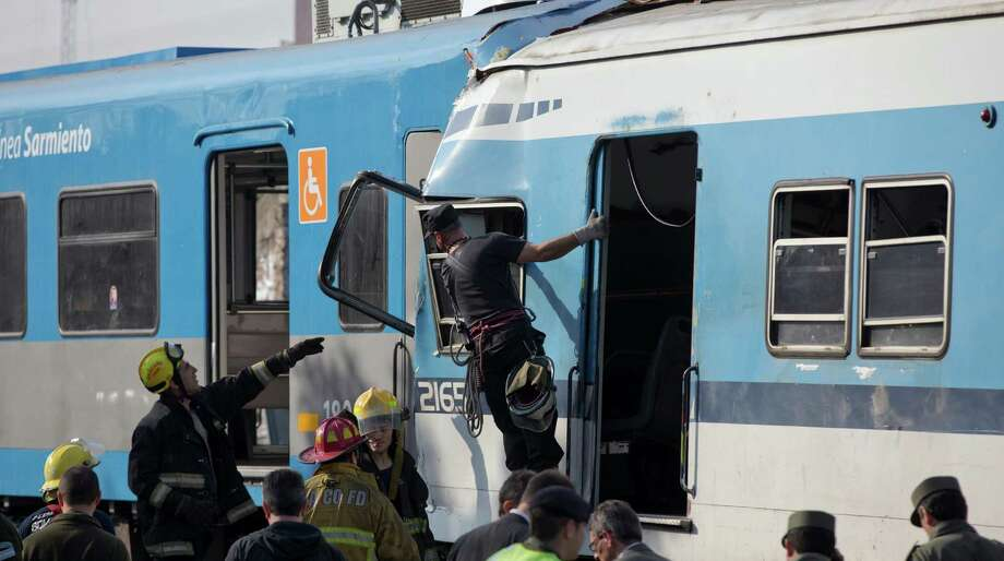 "Firefighters work to rescue trapped passengers from a commuter train on the outskirts of Buenos Aires, Argentina, Thursday, June 13, 2013. A two-level train slammed into another that had stopped between stations during the morning commute Thursday. Firefighters and police are pulling passengers from the wreckage. Train operator spokesman Pablo Gunning says there are ""various fatalities"" though has not specified how many. Photo: AP"