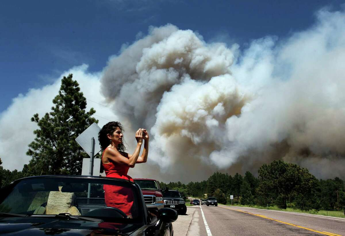 Colorado Springs resident Yolette Baca takes a photo of the wildfire in the Black Forest area north of Colorado Springs, Colo., on Wednesday, June 12, 2013.