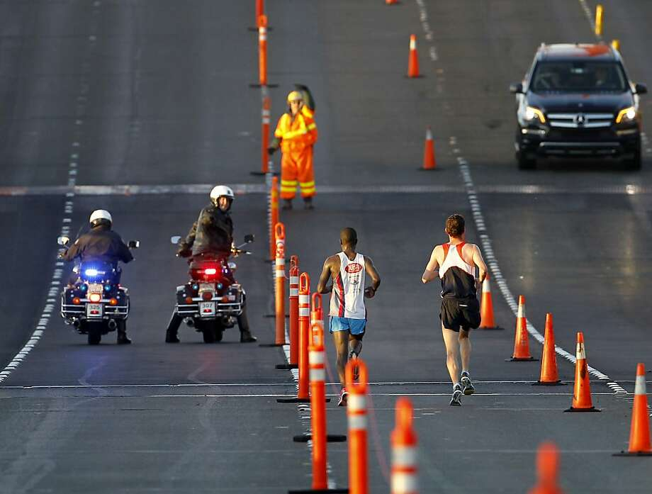 Golden Gate Bridge officials signaled for marathon leaders Francois Lhuissier (right) and Ismail Ssenyange to move over a lane as they started south on the bridge Sunday June 16, 2013. Thousands ran in the annual San Francisco Marathon, which was held earlier this year to accommodate the America's Cup races. Photo: Brant Ward, The Chronicle
