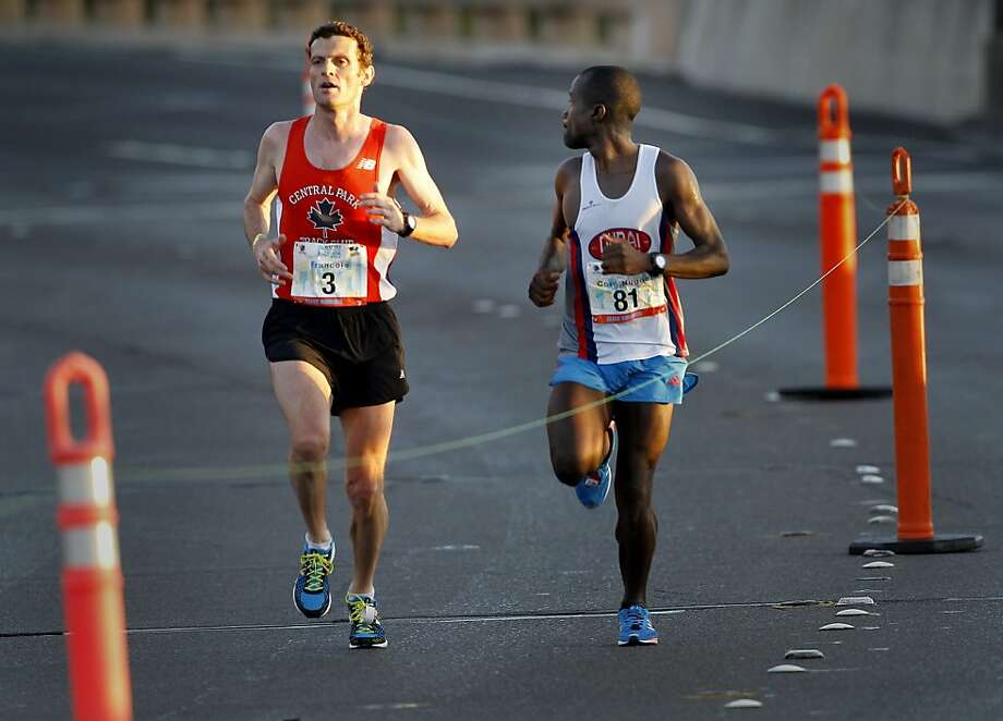 Second place finisher Ismail Ssenyange (right) looked over at eventual marathon winner Francois Lhuissier as they crossed the Golden Gate Bridge Sunday June 16, 2013. Thousands ran in the annual San Francisco Marathon, which was held earlier this year to accommodate the America's Cup races. Photo: Brant Ward, The Chronicle