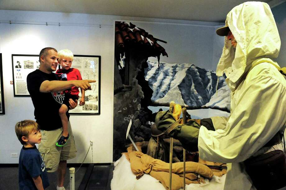 Jim Crossen and his sons, Caiden, 4, right, and Jack, 6, look at an exhibit honoring the 10th Mountian Division inside the Military Museum of Southern New England in Danbury, Conn. Sunday, June 16, 2013. Photo: Michael Duffy / The News-Times