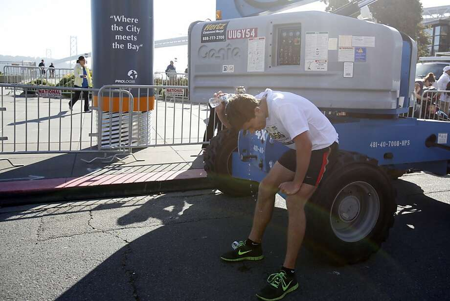 Nick Donald rests on a tire and pours water on his head after finishing the 2013 Wipro San Francisco Marathon in San Francisco, Calif. on June 16, 2013. Photo: Ian C. Bates, The Chronicle